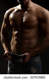 One handsome sexual strong young undressing man with muscular body in blue jeans holding hands on torso standing in studio on black background, vertical picture