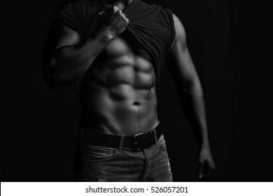 One handsome sexual strong young man with muscular body in jeans with shirt on shoulder standing posing on studio background black and white, horizontal picture