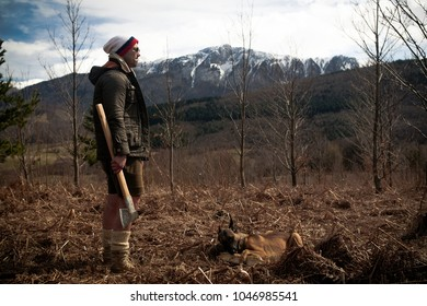 One handsome strong stylish male logger of young man holding wooden axe in forest outdoor and mountains in the background. Posing in front of a camera with his dog