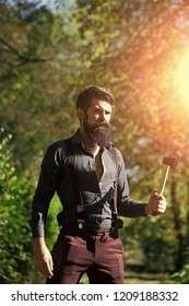One handsome strong stylish male logger of young man with long lush black beard and moustache in shirt holding wooden axe standing in forest outdoor on natural background, vertical picture