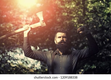 One handsome strong stylish male logger of young man with long lush black beard and moustache in shirt holding wooden axe standing near tree outdoor on natural background, horizontal