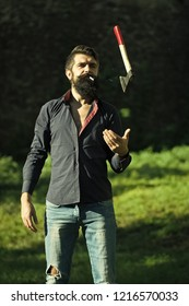 One handsome strong stylish male logger of young man with long lush black beard and moustache in shirt holding wooden axe standing near tree outdoor on natural background, vertical