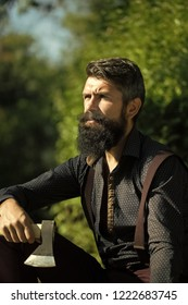 One handsome strong stylish male logger of young man with long lush black beard and moustache in shirt holding wooden axe sitting in forest outdoor on natural background, vertical picture