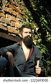 One handsome strong stylish male logger of young man with long lush black beard and moustache in shirt holding wooden axe standing near brick wall outdoor, vertical picture
