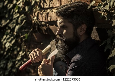 One handsome strong stylish male logger of young man with long lush black beard and moustache in shirt holding wooden axe standing near brick wall outdoor, horizontal picture