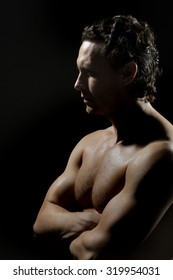 One handsome strong young stripped sweat muscular male model with curly hair and beautiful straight body standing in studio on black background, vertical picture