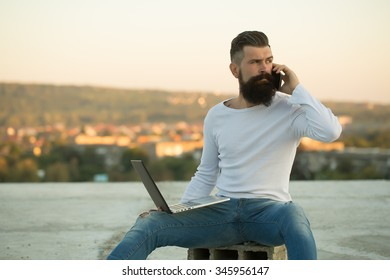 One handsome young bearded business man in white sweater holding and working on laptop talking on mobile phone outdoor on blurred natural background, horizontal picture