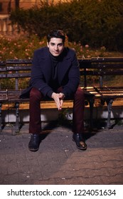 one handsome young man, 20-29 years old, posing, autumn clothes, sitting bench on city square. night time, dark.