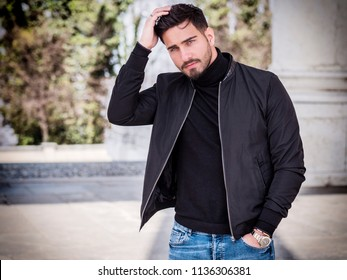 One handsome young man in urban setting in modern city, sitting, wearing black leather jacket and jeans