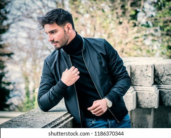 One handsome young man in urban setting in city, wearing black leather jacket and jeans
