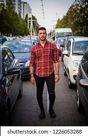 One handsome young man in urban setting in modern European city standing in the middle of the street among car traffic, looking at camera, wearing jeans and red checkered shirt