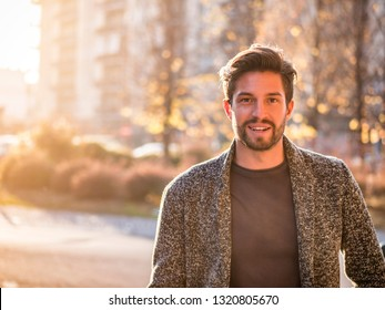 One handsome young man in urban setting in European city, standing and smiling to camera happy