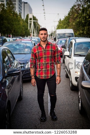 df7646d1 One handsome young man in urban setting in modern European city standing in  the middle of the street among car traffic, looking at camera, wearing jeans  and ...
