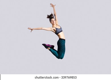 One happy attractive gorgeous young fit modern woman in aquamarine sportswear with ponytail working out, dancing, jumping with joy, full length, studio image on gray background
