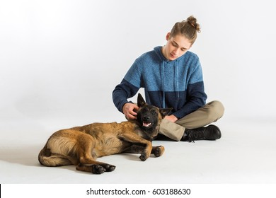 One happy calm young male Belgian Malinois puppy laying down on floor while being pet by a teenage boy. Teen boy giving loving attention to his dog.