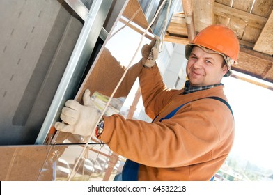 One happy construction worker builder installing big tile on a building facade