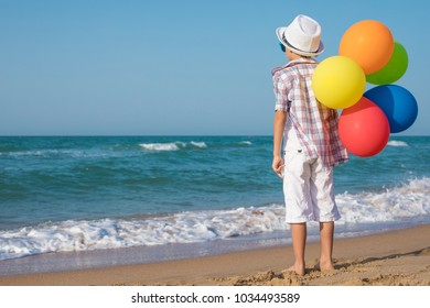 One happy little boy playing on the beach at the day time.  Kid having fun outdoors. Concept of summer vacation.