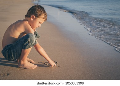 One happy little boy playing on the beach at the sunset time. He draws on the sand.  Kid having fun outdoors. Concept of summer vacation.