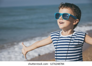 One happy little boy playing on the beach at the day time. He are dressed in sailor's vest. Kid having fun outdoors. Concept of sailor on vacation.