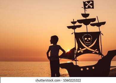 One happy little boy standing on the beach at the sunset time. He playing with a cardboard pirate ship.  Kid having fun outdoors. Concept of summer vacation.
