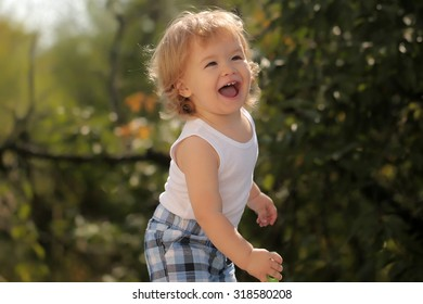One happy smiling small child boy with blonde curly hair standing in checkered shorts and white shirt sunny day outdoor on green natural background, horizontal picture