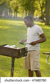 one happy twenties African American male cooking on a bbq grill outdoors in a park
