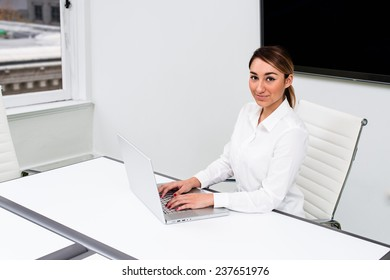 One Hispanic woman sitting at a table with a laptop.