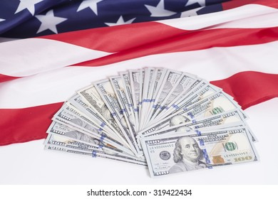 One hundred dollar bills with American flag background