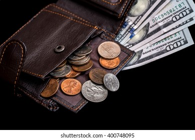 One hundred dollar bills in  dark leather purse isolated on black background