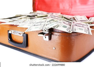 Lot of one hundred dollar bills in old suitcase isolated on white