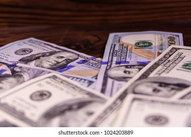 One hundred dollar bills on wooden table