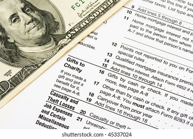 One hundred dollar bills sitting on tax papers, tax forms
