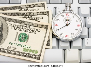 One hundred dollar bills sitting on a computer keyboard, making money online