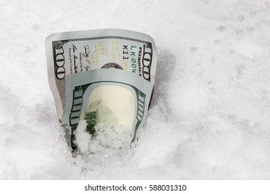One hundred dollar bills stuck in a snow bank