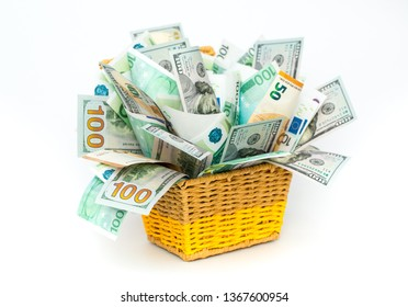One hundred dollar and euro bills are laid out creatively in a wicker basket. Beautiful original cash flow on a white background. Cash currency in the concept of accumulation. Finance and income.