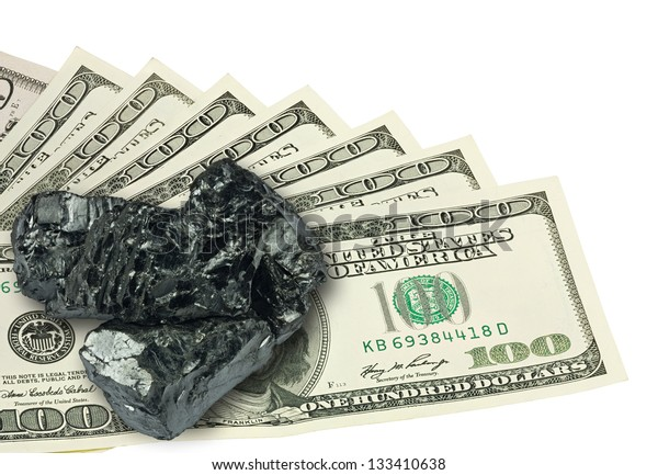 One hundred dollars banknote and raw coal on top