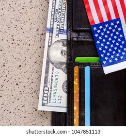 One hundred dollars banknote reach out out of a black old purse. And also part of the American flag. Square. Close-up.