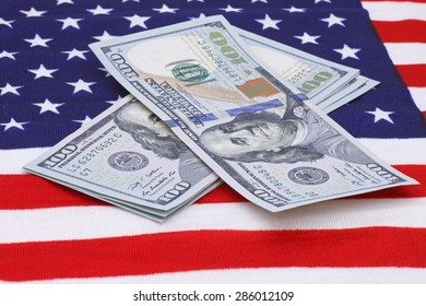 one hundred dollars banknotes on USA flag