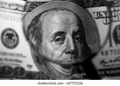 One hundred dollars in clip over magnifier lens. Finance concept