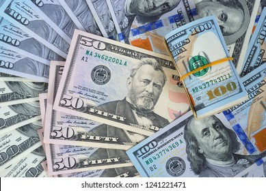 One hundred dollars and fifty dollars pile as background. American dollars cash money. One hundred dollar and fifty dollar banknotes.