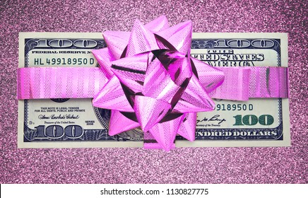 one hundred dollars gift wraped with a  purple ribbon on purple glitter background