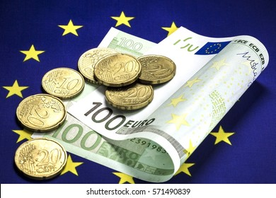 One hundred euro bill lying in the center of the star circle on the European community flag. Several euro cents coins on the bill. Macro image.