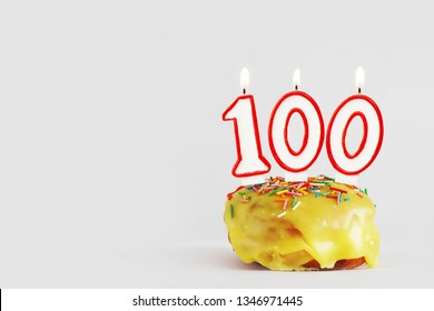 One hundred years anniversary. Birthday cupcake with white burning candles with red border in the form of 100 number. Light gray background with copy space