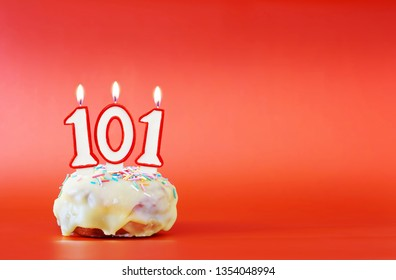 One hundred and one years birthday. Cupcake with white burning candle in the form of number 101. Vivid red background with copy space