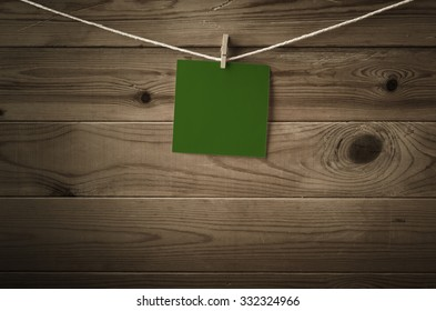 One individual square of festive dark green note paper, pegged to a string washing line with wood plank fence behind.  Low saturation and vignette gives a retro or vintage feel.