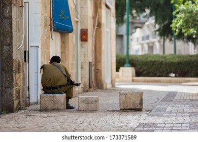 One israeli soldier sitting on the stone in Old Jaffa street. Sunny evening. Calmness and peace.