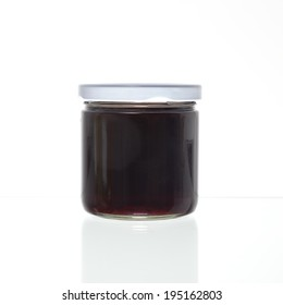 One jelly jar with no label against a white background and a slight reflection.