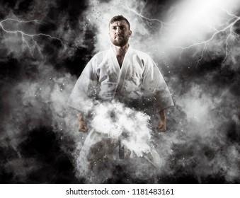 One judoka fighter man on dark smoke background
