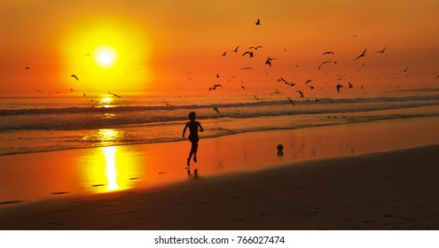 One kid running after a football at the beach, by the water line, silhouetted by background of a strong orange sunset, ocean waves and seagulls flying. Costa da Caparica, Lisboa, Portugal.