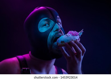 One kinky man, eating a cookie, as a sexy and kinky concept. mouth open, wearing a hood.